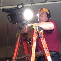 dave waldman on ladder with video camera